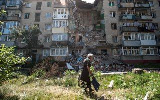 Μία γυναίκα περπατάει μπροστά από -κατεστραμμένο από το σφυροκόπημα- κτίριο του Σλαβιάνσκ.