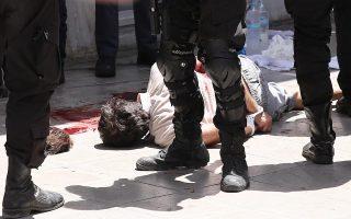 Ο επικηρυγμένος τρομοκράτης Νίκος Μαζιώτης κείται με χειροπέδες, τραυματισμένος στον δεξιό ώμο, επί της οδού Μητροπόλεως της Αθήνας.