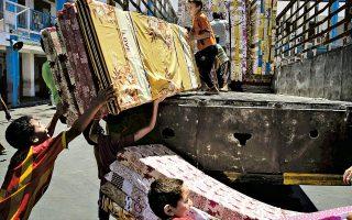 Παιδιά από βόρειες περιοχές της Γάζας που εγκατέλειψαν τα σπίτια τους ξεφορτώνουν στρώματα σε σχολείο του ΟΗΕ.