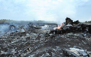 Τα συντρίμμια του Boeing 777 των Μαλαισιανών Αερογραμμών –στο οποίο επέβαιναν 295 άτομα– σιγοκαίγονται σε χωράφι κοντά στην πόλη Σακτάρσκ.