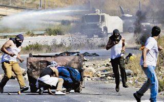 Παλαιστίνιοι διαδηλωτές στη διάρκεια χθεσινών ταραχών έξω από στρατιωτικές φυλακές του Ισραήλ στα περίχωρα της Ραμάλας, στη Δυτική Οχθη.