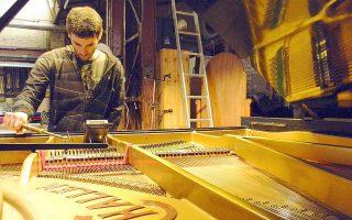 Ο συνθέτης και πιανίστας Αλέξανδρος Δρόσος χορδίζει ένα πιάνο προτού παραδοθεί στον ιδιοκτήτη του.