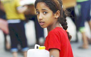 Μικρή Παλαιστίνια κουβαλάει πόσιμο νερό σε σχολείο της Γάζας, που έχει μετατραπεί σε καταφύγιο μετά τη νέα πολεμική επιχείρηση των Ισραηλινών.
