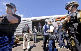 Ενοπλος αυτονομιστής καλύπτει το πρόσωπό του για να προστατευτεί από τη δυσωδία των σορών των θυμάτων από την κατάρριψη του αεροσκάφους των Μαλαισιανών Αερογραμμών στα σύνορα Ουκρανίας - Ρωσίας, καθώς οι επιθεωρητές του ΟΑΣΕ και Ολλανδοί εμπειρογνώμονες ελέγχουν τους σάκους που κείτονται στα βαγόνια ψύξης.