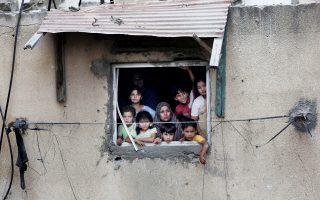 Παλαιστινιακή οικογένεια παρακολουθεί διασώστες που ψάχνουν επιζώντες στη Γάζα.