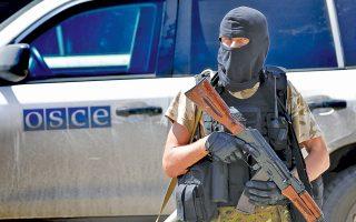 Mασκοφόρος ρωσόφωνος αυτονομιστής φρουρεί το όχημα της αποστολής του ΟΑΣΕ, ενόσω Ολλανδοί ειδικοί εξετάζουν τις σορούς των επιβαινόντων.