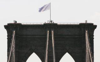 Οι αστυνομικές αρχές της Νέας Υόρκης στέκονται κάτω από τη λευκή σημαία, που ανεμίζει στον δυτικό πύργο της γέφυρας του Μπρούκλιν.