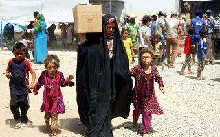 Οικογένειες Ιρακινών που εκτοπίστηκαν λόγω των εχθροπραξιών δέχονται ανθρωπιστική βοήθεια σε καταυλισμό έξω από το Αρμπίλ.