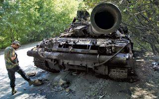 Ρωσόφωνος μαχητής παρατηρεί ένα κατεστραμμένο ουκρανικό τανκ. Οι μάχες στην περιοχή όπου συνερτίβη το Μπόινγκ ξανάρχισαν την Τετάρτη.