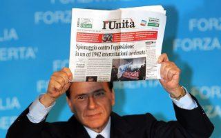 Φωτογραφία αρχείου με τον Μπερλουσκόνι να κραδαίνει με έκδηλη ειρωνεία τη L'Unita στη διάρκεια προεκλογικής του ομιλίας το 2006.