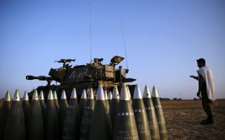 An Israeli soldier prays beside a mobile artillery unit and shells in a field near the central Gaza Strip July 11, 2014. Israeli air strikes on Gaza killed four more Palestinians before dawn on Friday, raising the death toll from the four day offensive to at least 85, while a Palestinian rocket hit a fuel tanker at a Israeli petrol station causing a huge blaze. REUTERS/Finbarr O'Reilly (ISRAEL - Tags: POLITICS CIVIL UNREST MILITARY RELIGION)
