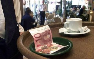 A Paris cafe waiter carries his tray with euro notes and coins Tuesday, Jan. 1, 2002, as the euro currency becomes legal tender in 12 European Union countries. (AP Photo/Franck Prevel)