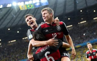 epaselect epa04306265 Germany's Toni Kroos (R) celebrates with his teammates Miroslav Klose (L) and Sami Khedira (bottom) after scoring a goal during the FIFA World Cup 2014 semi final match between Brazil and Germany at the Estadio Mineirao in Belo Horizonte, Brazil, 08 July 2014.   (RESTRICTIONS APPLY: Editorial Use Only, not used in association with any commercial entity - Images must not be used in any form of alert service or push service of any kind including via mobile alert services, downloads to mobile devices or MMS messaging - Images must appear as still images and must not emulate match action video footage - No alteration is made to, and no text or image is superimposed over, any published image which: (a) intentionally obscures or removes a sponsor identification image; or (b) adds or overlays the commercial identification of any third party which is not officially associated with the FIFA World Cup)  EPA/MARCUS BRANDT   EDITORIAL USE ONLY