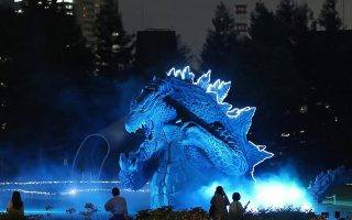 epaselect epa04319669 Passerby look at an illuminated 6.6 meter tall Godzilla replica during a press preview of the event 'Midtown meets Godzilla' at Tokyo Midtown, in Tokyo, Japan, 17 July 2014. The event will last from 18 July until end of August.  EPA/FRANCK ROBICHON