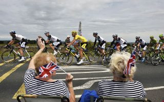 TOPSHOTSSupporters wave along the road as Germany's Marcel Kittel (C), wearing the overall leader's yellow jersey, rides past during the 201 km second stage of the 101th edition of the Tour de France cycling race on July 6, 2014 between York and Sheffield, northern England.  AFP PHOTO / JEFF PACHOUD