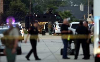 epa04308901 Police officers and SWAT team members surround an area following a reported shooting incident in Spring, Texas, USA, 09 July 2014. Reports state that police were called to the scene after six people, including four children, were shot and killed.  EPA/AARON M. SPRECHER