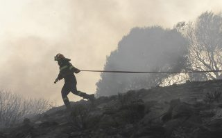 Πυροσβέστης βοηθάει στην κατάσβεση της φωτιάς που καίει δασικές εκτάσεις στην περιοχή της Κερατέας ( Φωτογραφία: Ορέστης Παναγιώτου /ΑΠΕ-ΜΠΕ).