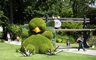 People pass near a creation by French artist and children's book author Claude Ponti on July 8, 2014 in the botanical garden of Nantes, western France, displayed as part of the