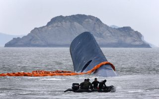 A vessel involved in salvage operations passes near the upturned South Korean ferry