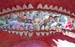 Children of a kindergarten admire the giant mouth of a primeval Megalodon  shark model  at  the Natural History Museum in Schleusingen, central Germany, Friday, July 4, 2014. The model is part of the special  exhibition 'Sharks' .  (AP Photo/Jens Meyer)
