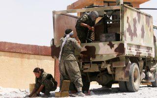 Μέλη των Κουρδικών Μονάδων Λαϊκής Προστασίας (YPG) ετοιμάζουν τον εξοπλισμό τους κατά τη διάρκεια της σύγκρουσης με τους εξτρεμιστές του Ισλαμικού Κράτους στα σύνορα του Ιράκ με τη Συρία, κοντά στην πόλη Ελιερμπέχ.