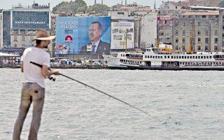 Ενας άνδρας ψαρεύει κοντά στον Βόσπορο. Στο φόντο φαίνεται αφίσα του Τούρκου πρωθυπουργού Ερντογάν.