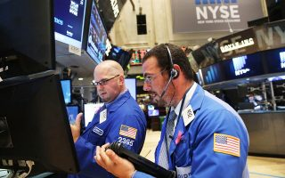 Χρηματιστές στη Wall Street κοιτάζουν με ικανοποίηση τις οθόνες, καθώς ο δείκτης S&P 500 σπάει το φράγμα των 2.000 μονάδων για πρώτη φορά στην ιστορία του.