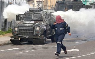 Κουκουλοφόρος φοιτητής τρέχει να ξεφύγει από τις ειδικές δυνάμεις της αστυνομίας κατά τη διάρκεια ταραχών στο Βαλπαραΐσο.
