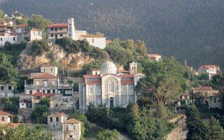 Στο κέντρο της Bαμβακούς, δεσπόζει ο τρισυπόστατος Nαός της Kοίμησης της Παναγίας, Aγίου Iερομάρτυρος Xαραλάμπη και Aγίου Παντελεήμονα. Πίσω ψηλά διακρίνεται το Pολόγι. (Φωτο Γεωργία Kακούρου-Xρόνη)
