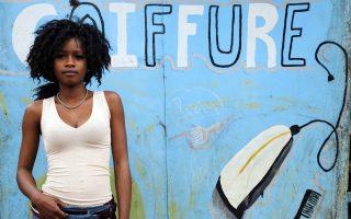H νεαρή Bandele Kadjatou ποζάρει μπροστά στην είσοδο κομμωτηρίου.