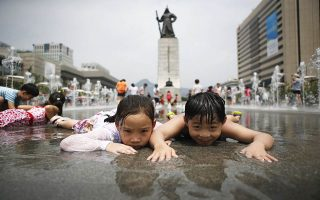Children play in a fountain to cool down on a hot summer day in front of the General Lee Soon-shin statue in Gwanghwamun, Seoul July 28, 2014.   REUTERS/Kim Hong-Ji (SOUTH KOREA - Tags: ENVIRONMENT SOCIETY TPX IMAGES OF THE DAY)