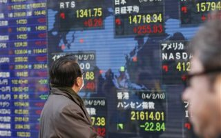 A man looks at an electronic stock indicator showing global stock prices including Japan's benchmark Nikkei 225, top center, which gained 255.93 points, or 1.77 percent, and closed at 14,718.34 in Tokyo Monday, Feb. 10, 2014. Asian stock markets were mostly higher Monday as investors looked ahead to Janet Yellen's first comments before Congress as the new Federal Reserve chairwoman. (AP Photo/Shizuo Kambayashi) (AP Photo/Shizuo Kambayashi)