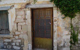 Η πόρτα, σχεδόν ξεχαρβαλωμένη και μισάνοιχτη.