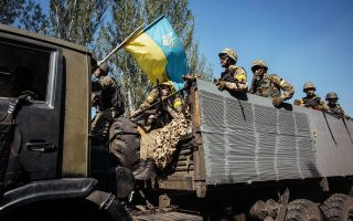 epa04348504 Ukrainian soldiers ride on a military truck during fighting against militants, close to Ilovaysk town, near of Donetsk, Ukraine, 10 August 2014. Ukrainian government forces have narrowed the ring around Luhansk and the other rebel stronghold in Donetsk. Artillery attacks continued throughout the night in northern Donetsk.  EPA/ROMAN PILIPEY