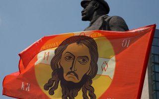 Η σημαία του «Ρωσικού Ορθόδοξου Στρατού», μιας ένοπλης ομάδας ρωσόφωνων, κοσμεί το άγαλμα του Λένιν στο Ντονέτσκ.
