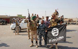 Σιίτης μαχητής κρατάει σημαία του Ισλαμικού Κράτους την οποία κατάσχεσε στη διάρκεια επιχείρησης έξω από το Αμερλί, βόρεια της Βαγδάτης.