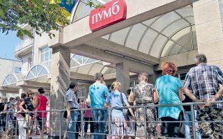 Kάτοικοι της Μαριούπολης περιμένουν στην ουρά έξω από τράπεζα για να πάρουν τις καταθέσεις τους, καθώς δεν γνωρίζουν τι θα συμβεί αύριο.