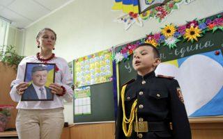 Πρώτη μέρα στο σχολείο 1. Ο νεαρός μαθητής της στρατιωτικής σχολής απαγγέλλει από μνήμης ένα ποίημα  για  τα παιδιά του Κιέβου που  έκαναν  ένα μάθημα «κουράγιου». Ο νεαρός καλεσμένος από το στρατιωτικό σχολείο τους εμψύχωσε  και η δασκάλα κρατούσε την φωτογραφία του νέου προέδρου Petro Poroshenko στην αγκαλιά της, σε μια αναγκαία για την χώρα, δήλωση πίστης στην πατρίδα.  EPA/TATYANA ZENKOVICH