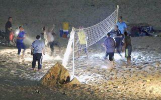 Νεαροί Παλαιστίνιοι παίζουν μπιτς βόλεï, υπό το φως των μοτοσικλετών τους, σε παραλία της βόρειας Γάζας.