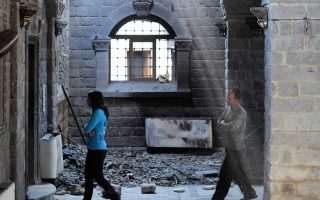 Πολίτες της Χομς περπατούν μέσα σε εκκλησία της πόλης, από την οποία αποσύρθηκαν οι αντάρτες.