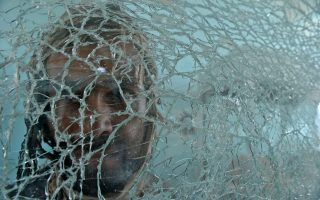 An Afghan bystander is seen through shattered glass at the scene of the September 4 suicide attack on a government compound in Ghazni, during a media tour of the area on September 13, 2014. A Taliban attack September 4 on a government compound killed 13 security personnel and left at least 60 other people wounded when a truck bomb triggered hours of fighting, officials said. About 20 insurgents armed with machine guns and grenade launchers were also killed during the assault on the intelligence agency base in Ghazni province, one of the most volatile regions of Afghanistan. AFP PHOTO/SHAH Marai