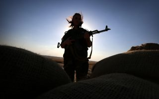 TOPSHOTS An Iranian Kurdish female member of the Freedom Party of Kurdistan (PAK) keeps a position in Dibis, some 50 kms northwest of Kirkuk, on September 15, 2014. The world's top diplomats pledged today to support Iraq in its fight against Islamic State militants by
