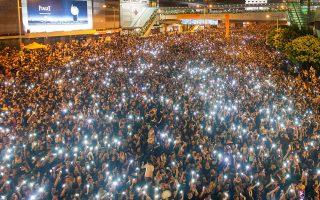 Χθεσινή διαδήλωση ακτιβιστών, που κρατούν τα κινητά τους τηλέφωνα, κοντά στην έδρα της κυβέρνησης του Χονγκ Κονγκ.