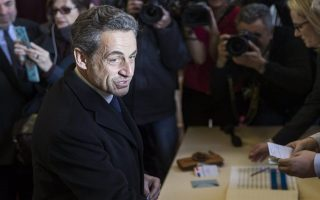 epa04137388 Former French President Nicolas Sarkozy votes at the Lycee Jean De La Fontaine during the first round of the municipal election in Paris, France, 23 March 2014. The first round of France's two-stage municipal elections got under way 23 March as losses were predicted for the Socialists under President Francois Hollande. Voters in 37,000 cities began casting their ballots in what is widely seen as the first test at the polling booth for Hollande since he took office nearly two years.  EPA/ETIENNE LAURENT