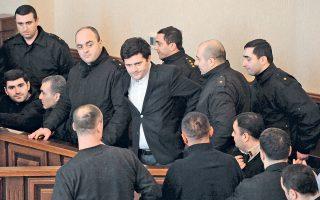 Πάνω: Ο 33χρονος David Akhalaia κατηγορείται από την κυβέρνηση της Γεωργίας για τη βίαιη ανάκριση δύο αξιωματούχων το 2005, για τέσσερις ανθρωποκτονίες και τον βασανισμό δύο ακόμα ανδρών. Κάτω, η αίτηση για πολιτικό άσυλο που υπέβαλε τον Μάιο στις ελληνικές αρχές.