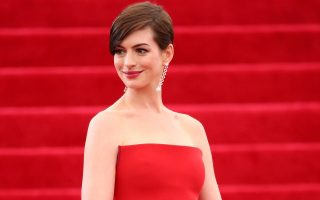 Anne Hathaway waves and blows kisses to the fans while arriving at the Met Gala in NYC