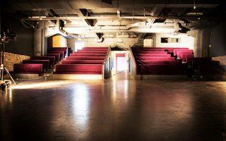 Η μεγάλη κεντρική σκηνή της «Ακαδημίας Πλάτωνος» συνδυάζει το παλιό με το νέο. Ξύλο, πέτρα, κόκκινο βελούδο στους πάγκους.