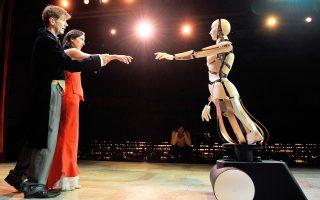 Πρόβα από το μιούζικαλ «Τα ρομπότ»: η μηχανή ακραγγίζει τον άνθρωπο, όπως περίπου ο Αδάμ τον Δημιουργό του στην Καπέλα Σιξτίνα του Μιχαήλ Αγγελου.