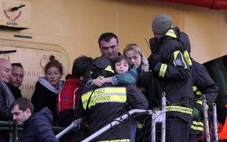 Ενα παιδί στην αγκαλιά Ιταλού πυροσβέστη αποβιβάζεται σώο στο Μπάρι με άλλους επιβάτες που γλίτωσαν από το «Norman Atlantic».