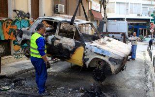 Συνεργεία του Δήμου της Αθήνας απομακρύνουν καμμένο αυτοκίνητο στην οδό Οικονόμου στα Εξάρχεια μετά τα επεισόδια που σημειώθηκαν το απόγευμα του Σαββάτου μετά την λήξη της πορείας μνήμης στον Αλέξη Γρηγορόπουλο, Κυριακή 7 Δεκεμβρίου 2014. ΑΠΕ-ΜΠΕ/ΑΠΕ-ΜΠΕ/Παντελής Σαίτας